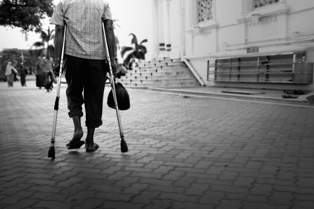 back of man standing using crutches, Aceh province, Indonesia